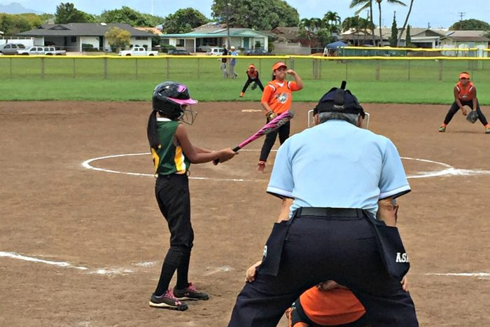 Photo of Lanai girl wearing jersey and swinging bat on softball field.